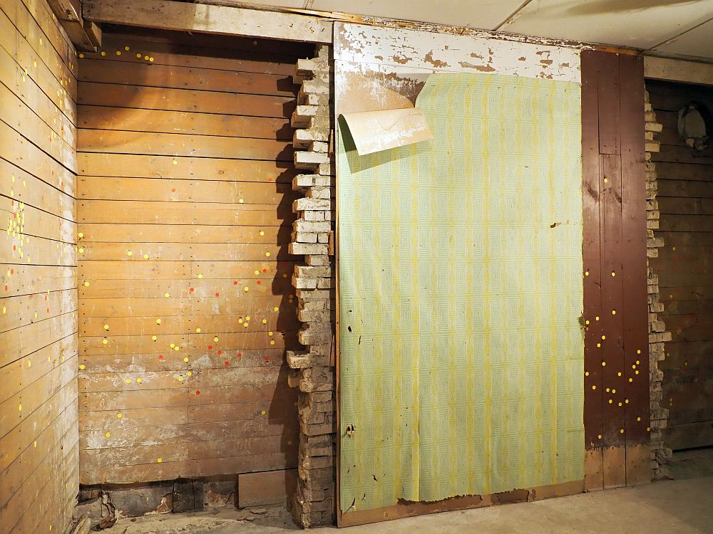 The wall has visible layers. About a third of it is horizontal wooden boards on the left. The middle half is brick in front of the wooden layer, so the brick wall ends with an uneven vertical cut. In front of the brick is another layer - wood or drywall or something, that has peeling, light green wallpaper on it. On the right is a small section of more wood, this time on top of the brick rather than behind it. Here the wood boards are vertical. All over both wood layers are little yellow and some red dots.