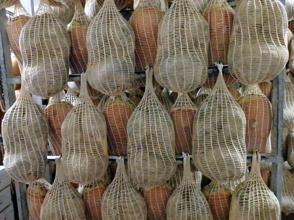 Parma hams in net bags hanging to dry on a rack.