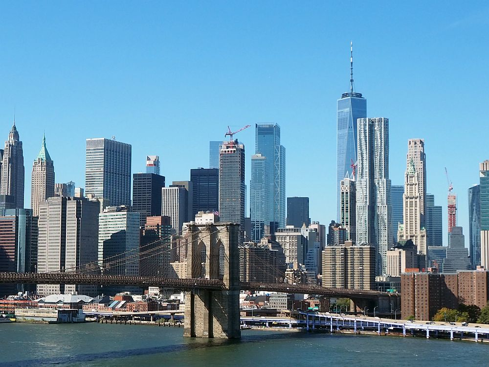 In the foreground, the river, with one of the Brooklyn Bridge's support towers and about half the bridge visible. Behind that, lots of skyscrapers, mostly in rectangles.