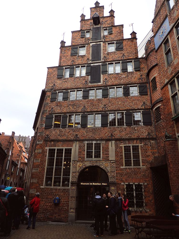 A tall (7-8 stories) narrow red-brick building with black shutters on the windows. The center doorway is arched, and some of the windows up the center are actually doors.
