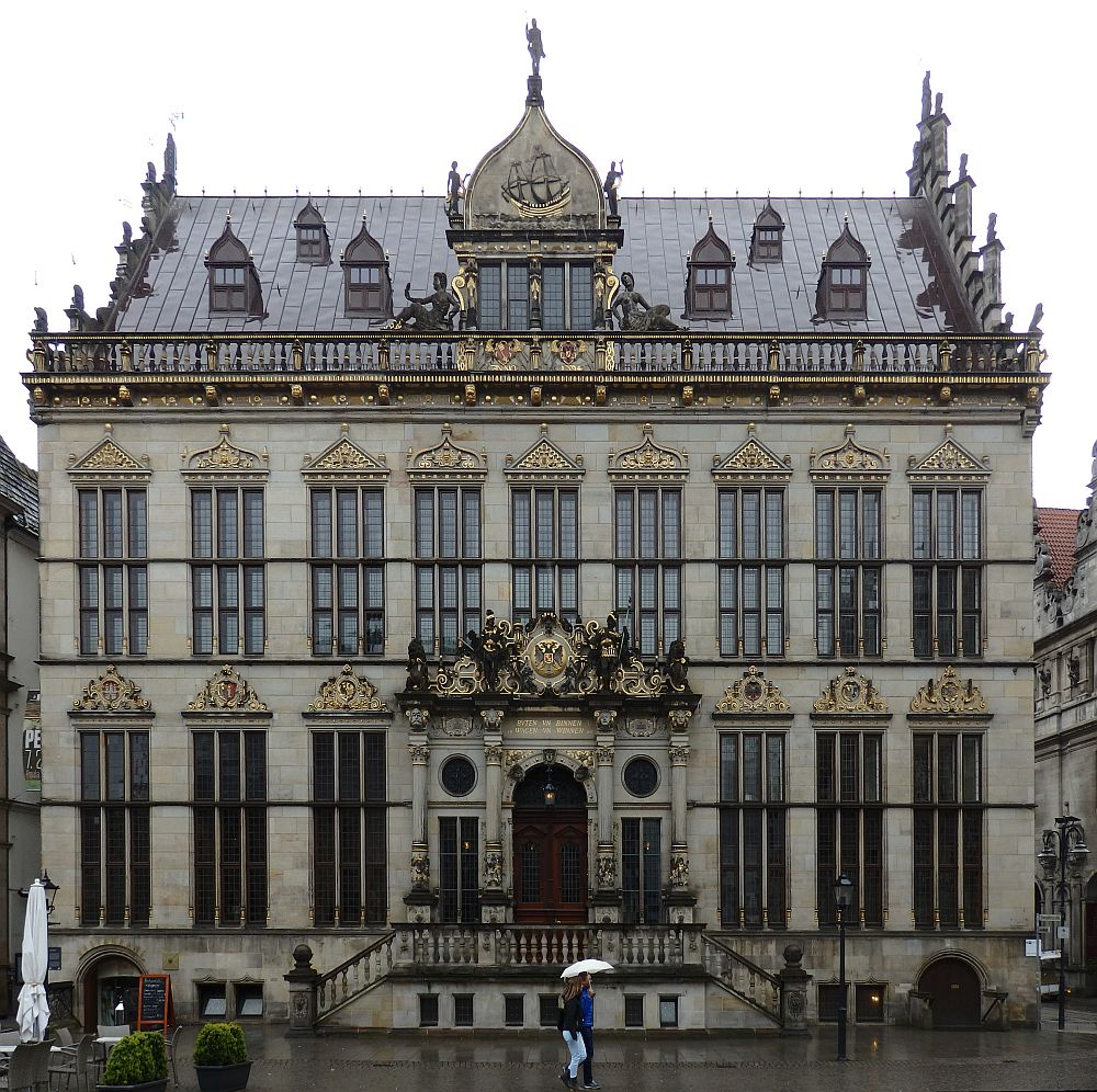 A grand facade: grey bricks with ornate decorations above each window, around the roof line and especially over the central doorway. The building is symmetrical, with the doorway in the center, three windows on either side on the ground floor and 9 windows on the upper floor. There are small dormer windows in the roof and a big one centered with a point above it holding a figure of a man. a stairway leads up to the front door from each side.