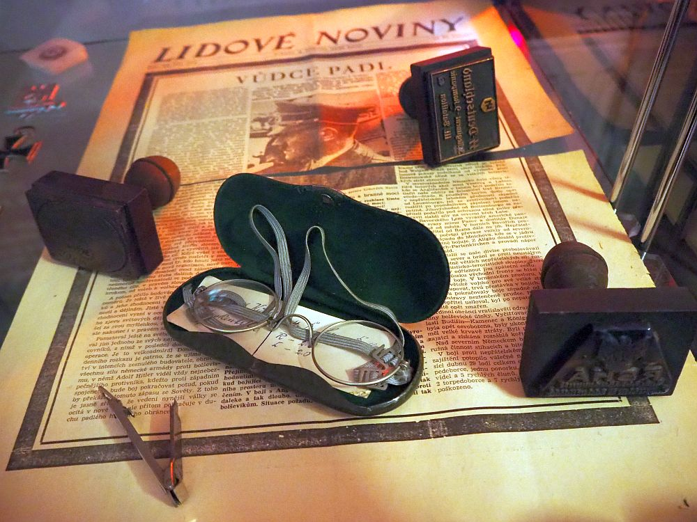 """The newspaper underneath is in Czech, titled """"Lidove Noviny"""". The article's title is """"Dudce Padl"""" and the only photo of the page is of Hitler. On top of the paper is an open glasses case with small round wire-rimmed glasses, three stamps and a tie pin."""