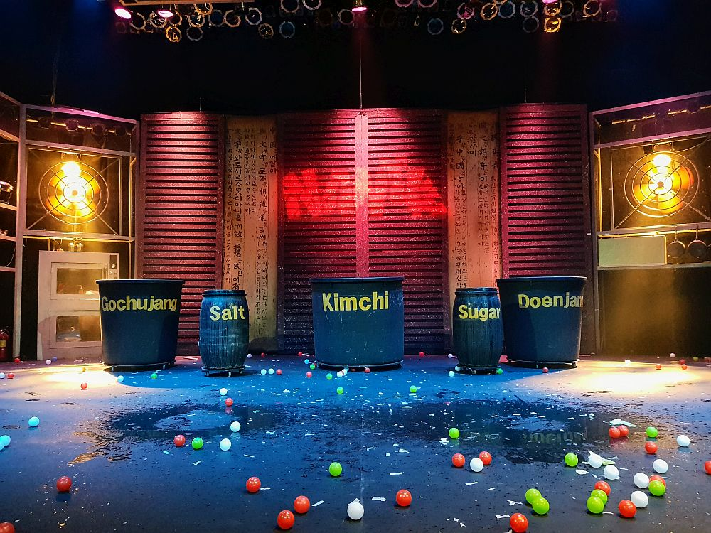 The stage of the Hongdae Nanta Theatre in the Hongik University Street neighborhood. There are no people on the stage, but the word Nanta is spraypainted on the back wall. In front of the wall are 4 big barrels of various sizes, each labeled: GochuJang, Salt, Kimchi, Sugar and Doenjan. Between them and the camer are scattered small balls: red, white and green, on a black wet floor that looks like it's wet in spots.