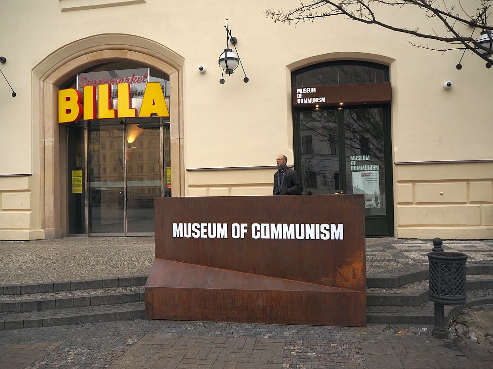 """A plain metal sign reads """"Museum of Communism"""". Behind that is the simple entrance to the museum. To the left of the entrance is a bigger arched door, with big letters proclaiming """"BILLA"""": the entrance to a supermarket. One man, my husband, stands in front of the museum entrance, waiting for me to finish taking pictures."""