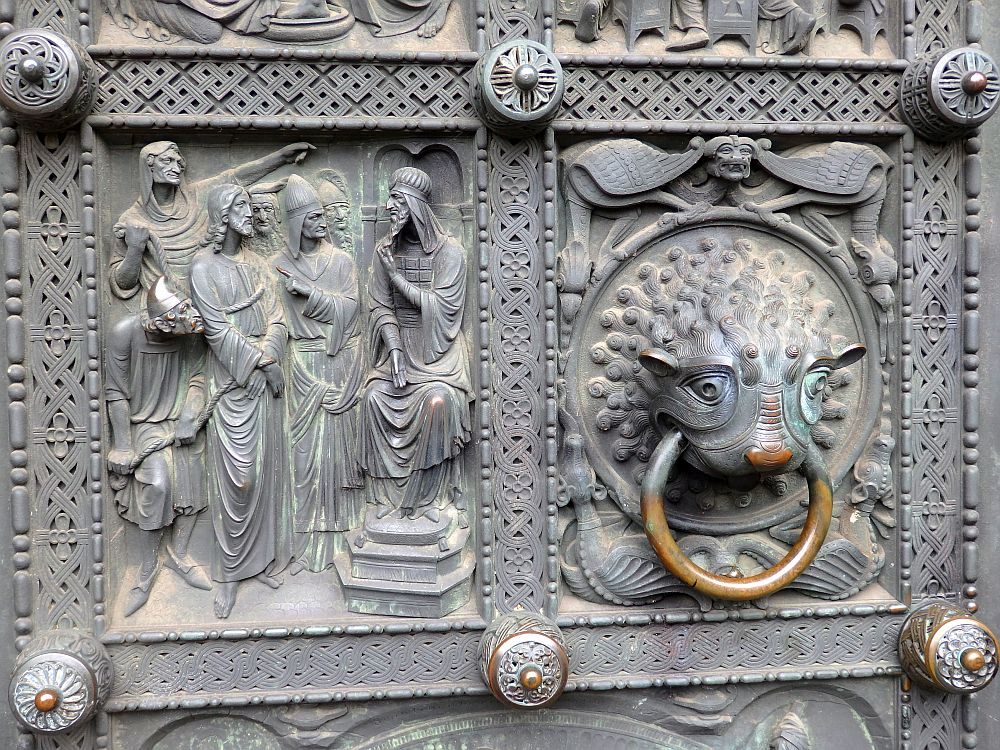 Detail of the metal door. The left panel is a bas-relief showing a person (Jesus?) sitting on a throne, speaking to a group of men. The right panel is the door knocker: a creature, maybe a lion, with the ring of the knocker in its mouth.