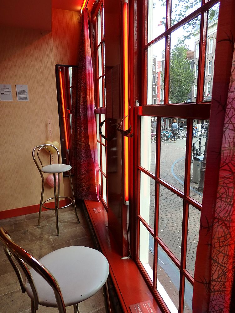Two high chairs, like barstools with backs, stand in front of two very tall windows that look out on the street.