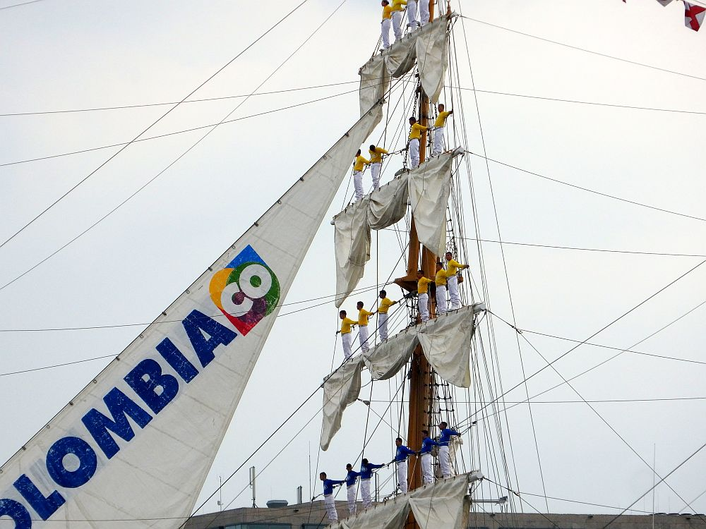 A close up of a mast of a tall ship, marked as Colombia on the one sail that is open. Along each horizontal strut, standing on the furled sail hanging from each strut, is a line of men. The top three rows (6, 4 and 4 people) wear white pants and yellow shirts. The bottom row (6 people) wears white pants and yellow shirt.