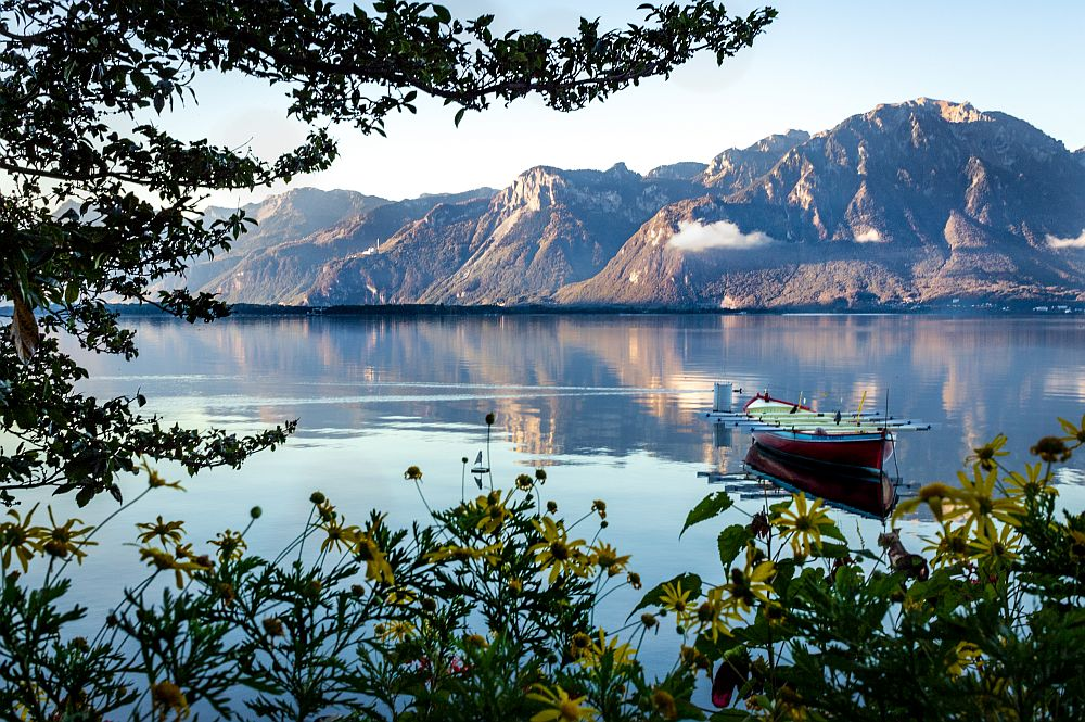 scenic view of a row boat on a lake with mountain background