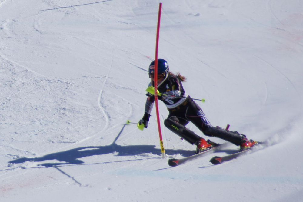 Shiffrin, in a black ski suit, a black helmet and red ski boots, swooshes around a red pole. She is leaning and clearly moving very fast.