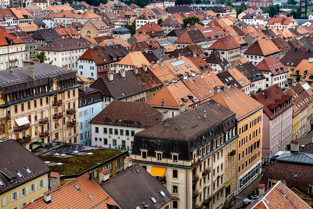 Buildings seen from above and to the side, in neat rows, mostly with red roofs and facads in shades of white and pastels.