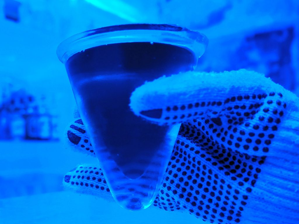 The photo, all very blue, is a closeup of my hand, gloved, holding a an ice glass with a dark liquid in it. The class is an upside-down cone shape.