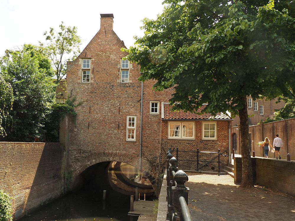 Another canal-like stream flowing under an archway with a brick bulding on top of the arch. This building is two stories tall. On the left is a brick wall with treetops visible beyond it. On the right is a walkway with a railing along the stream. Further to the right at the edge of the picture is a road, and two people walk down the road.