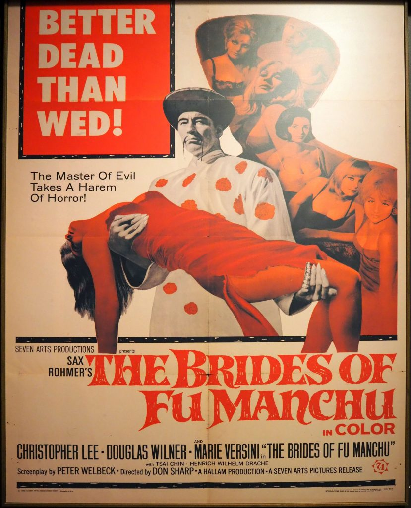 In the center is an image of the Fu Manchu character, looking at the camera, wearing a white robe with red polka dots. He has a mustache that hangs long and thin on either side of his mouth. He wears a wide-brimmed hat. He carries a woman under her back with one hand and under her knees with the other. She is dressed all in red, including red tights, and appears to be unconscious, with her ams and head dangling. Behind is an image of a group of women, all white, mostly dressed in bras. They look at the camera but do not appear to be afraid, but rather alluring. The text at the top says: Better dead than wed! The Master of Evil Takes A Harem of Horror! Below the image it says: Sax Rohmer's The Brides of Fu Manchu in Color, followed by a list of the main actors: Christopher Lee, Douglas Wilner, Marie Versini.