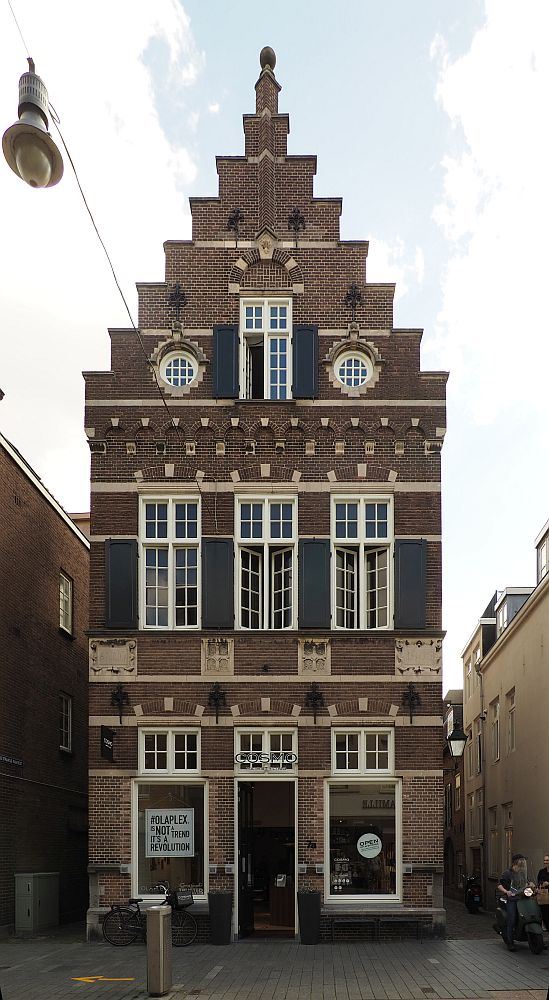 A tall, narrow red-brick building with a step gable. It is three stories tall. On the ground floor, a doorway in the middle and a window on either side of it. Three windows on the story above that. On the top story is one central rectangular window (like the others but smaller) flanked by two round windows.