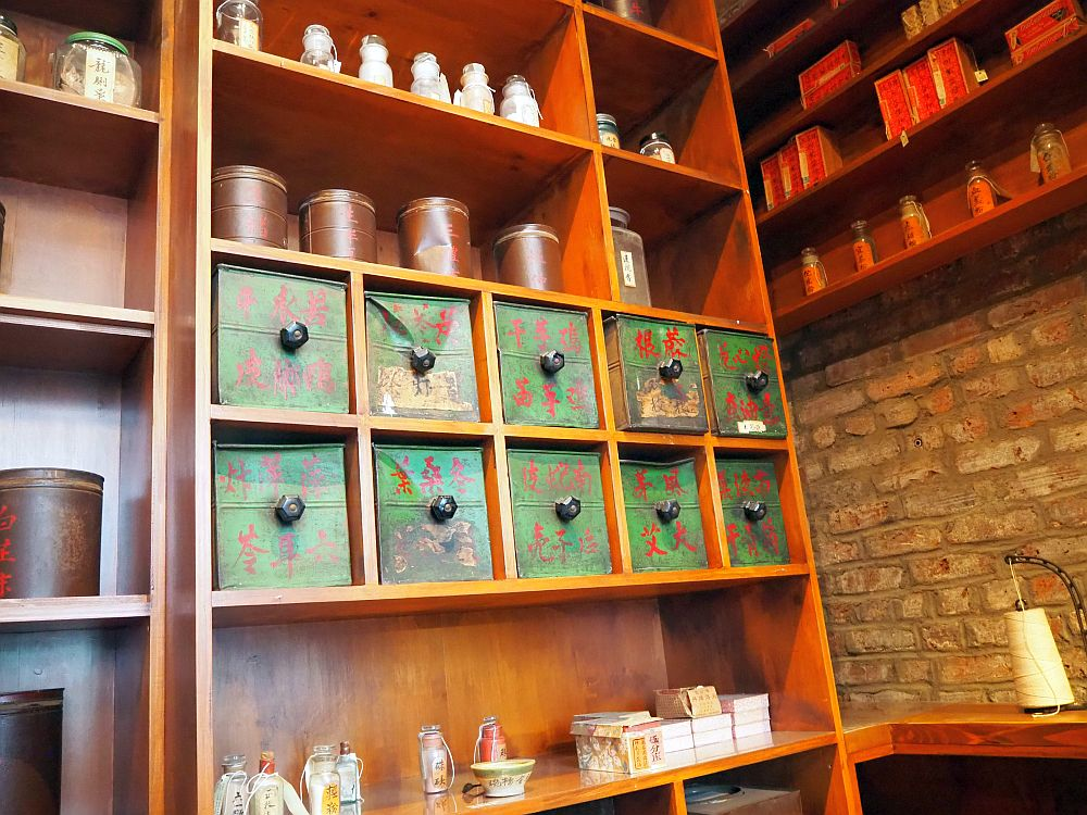 Neat brown wooden shelving, divided in squares and rectangular shelves. The middle ones are 5 squares across, each with a small bin inside it. The bins all have a round know in the center and are painted green with red Chinese lettering. Above and below, various other container: jars, pots and boxes, neatly spaced on the shelves.