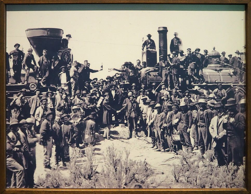 On the left and the right are two steam locomotives, pointed at each other. A crown stands in front of and on top of the locomotives, all white men, almost all facing the camera. In the middle, between the two engines, two men shake hands, also while looking a tthe camera.