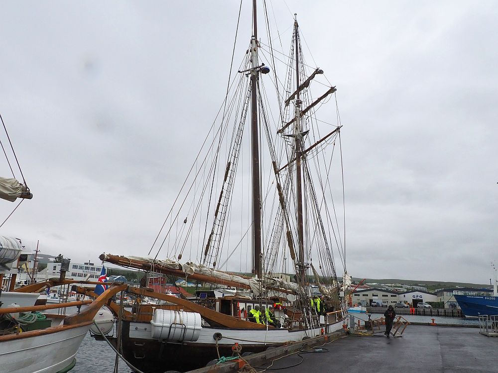 The ship is long and narrow, painted white around the sides but darker further down. It is moored along a pier. It has two masts, each with a web of rigging but the sails are all furled along the spars and booms. Grey cloudy sky behind.