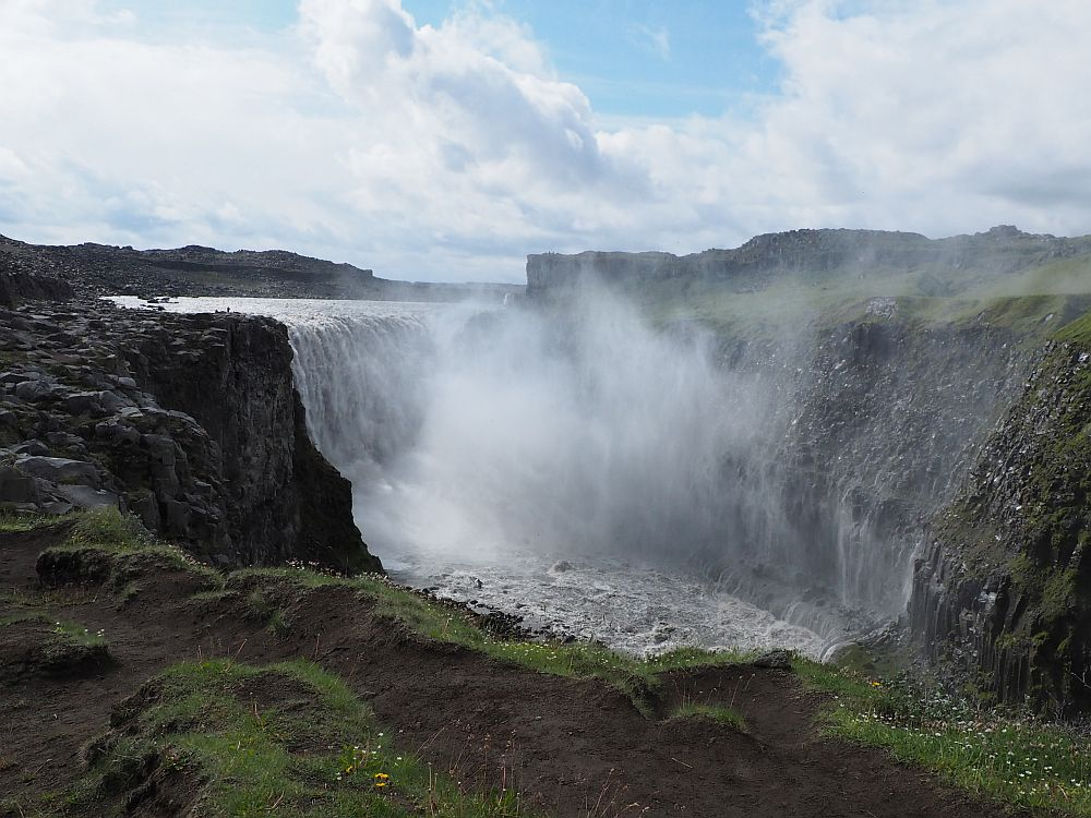 The wide waterfall and the canyon it cuts through, cliffs on both sides. The waterfall itself is hard to see with all the mist it churns into the air.