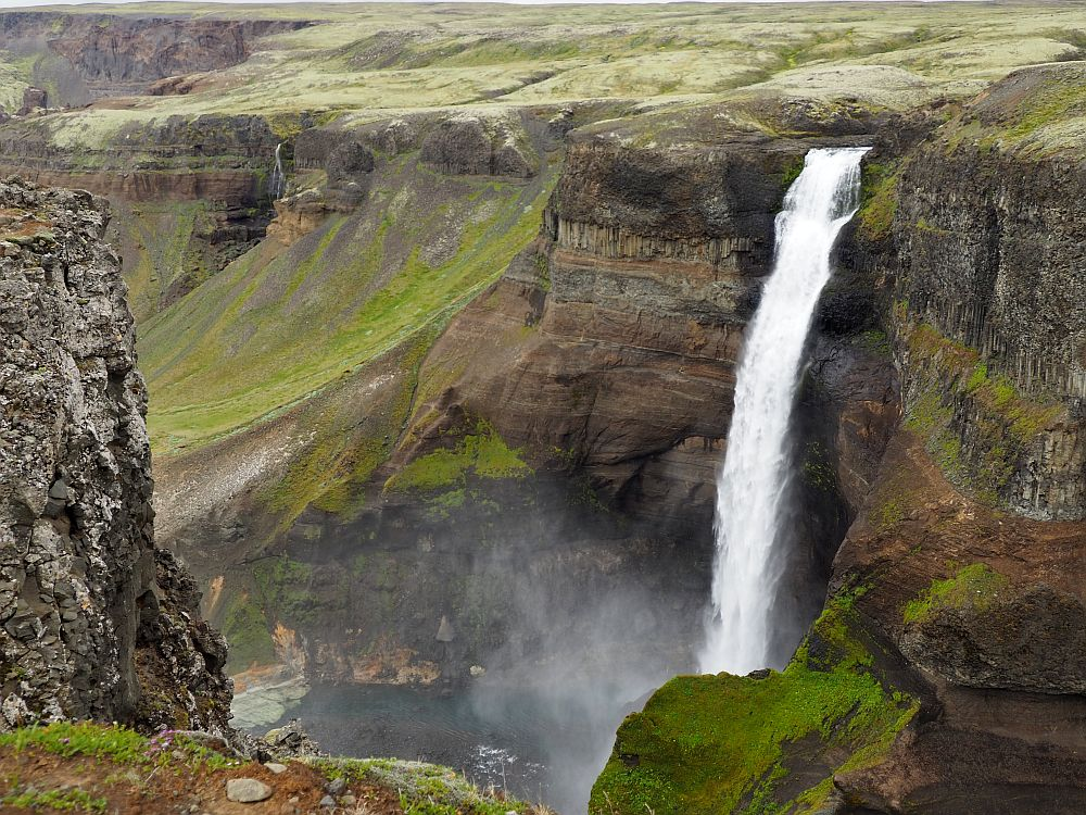 A long narrow white waterfall plunges off a cliff on the opposite side of a deep canyon. The bottom of the falls is not visible.
