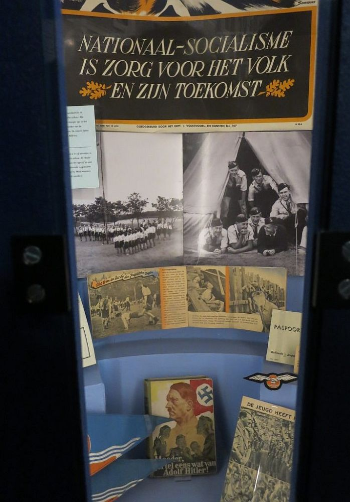 The display is tall and narrow. At the top is the slogan translated in the caption. Under that, photos of Nazi youth lined up in a field on the left and a group of young men in informal uniforms looking out of a tent and smiling on the right. Below that, some publication open to a page of photos of Nazi youth doing activities. On the floor of the display stand several books.