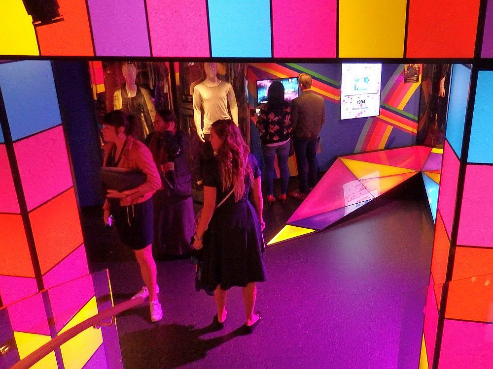 The entrance, looking down at it from upstairs, is framed in brightly-colored cubes of glass, lit from within. Beyond the entrance several visitors are visible.