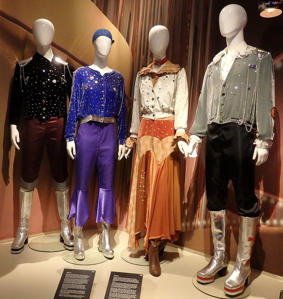 L-R: clothing on mannequins Bjorn's outfit is black with shiny stars on the shirt and silver-colored shoulder plates. Knee-high boots in silver with platform heels. Agnetha's outfit is a blue top with silver spots and purple pants with a shiny purple frill above the ankles. Silver platform boots. Frida's outfit: off-white shirt with multi-colored spots and a brownish collar, orangy-brown flowy skuirt to above the ankles, brown boots. Bennie's outfit: silver-gray jacket with shiny spots over a white shirt with a big collar, black pants tucked into high silver platform boots.