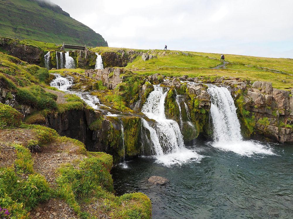 A green hillside, and the white waterfalls move down a series of stone steps, separated into several different streams before the all empty into one pool below.