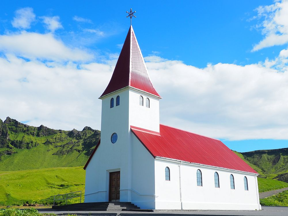 The church is simple with plain white sides and a bright red roof on the church and the steeple. The steeple is square with a few small windows near the top. The windows along the sides of the church are arched at their to ends.