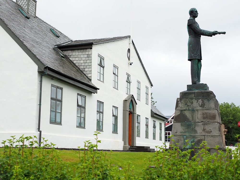 Seen from the side, looking along the front, the house is white with a grey roof and remarkably plain. Only two stories, it appears to be relatively small too. A statue stands in front of the house of a man, holding out a document in front of him.