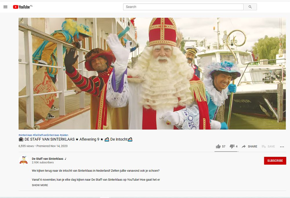 Sinterklaas faces the camera, waving his hand. He has a long beard and a red and gold mitre on his head. He wears a red and gold robe and white gloves. Two Petes are visible behind him to the left and right. Both are dressed in colorful outfits. Both have their natural white skin. The one on the left waves at the camera. The one of the right smiles.