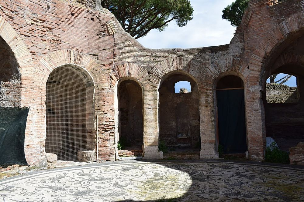 Arches surround the room in curve, open to the sky. The arches are made of brick rather than stone. The round floor is covered in a mozaic that is just grey and white and has a number of figures of animals.