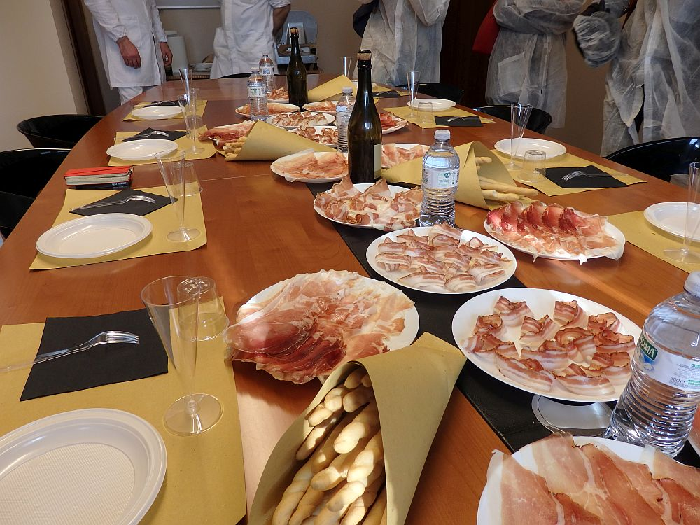 A long table set with plastic plates around it. In the middle are a number of plates, each covered with cold cuts, each a bit different from each other. A bag in the foreground has bread sticks and here and there are bottles of wine and water.