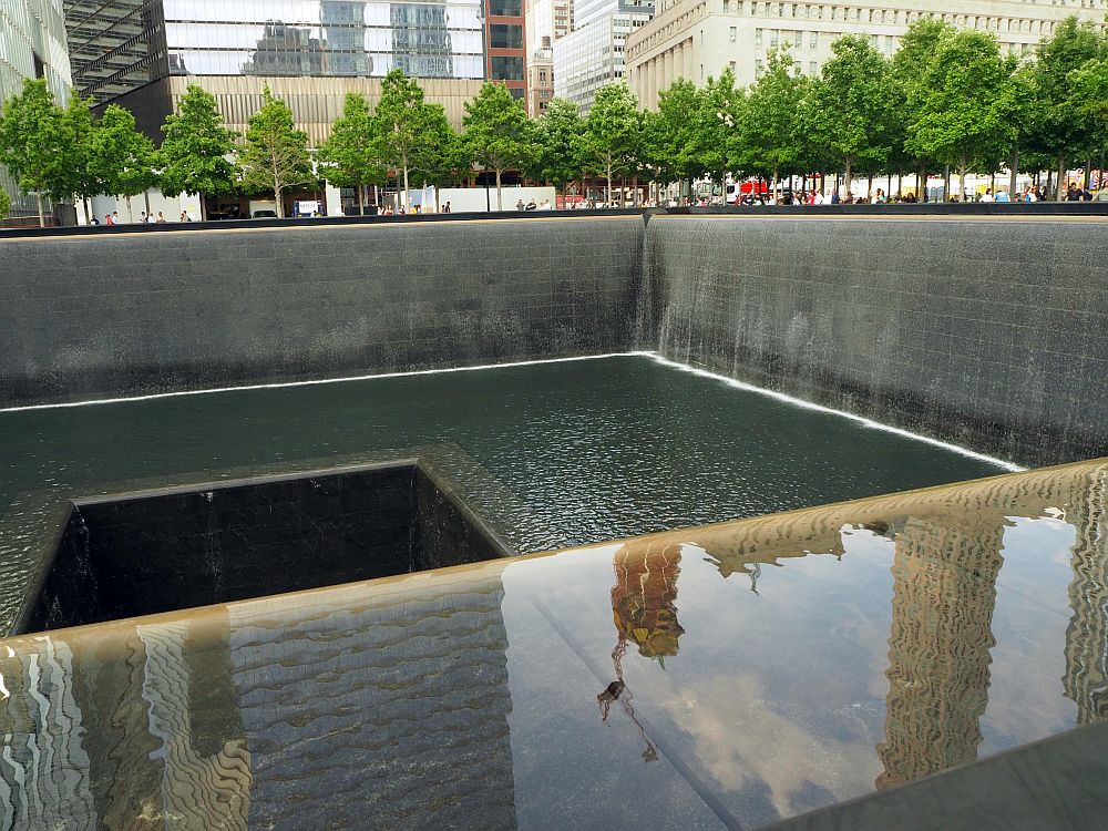 As described in the text. At the 9/11 memorila site, a square hole, with a square hole in its middle. Only two of the sides are visible, since the photo only shows one end of the fountain. The sides and bottom are dark gray. Water falls along both visible sides, but barely visible because it falls in a smooth curtain of water. People are visible on the other side, but extremely small, and only their heads and shoulders.