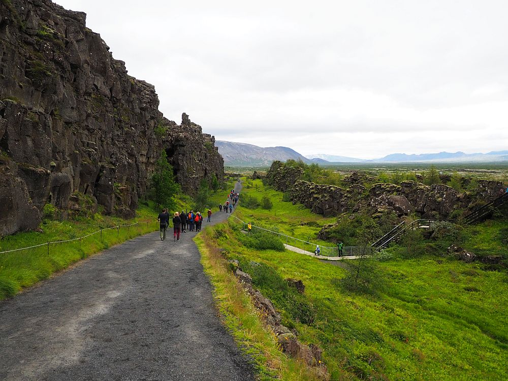 A wide grey gravel path stretches ahead, with a few people visible on it in the distance. On the left, a steep craggy cliff in black stone. On the right, a green slope down and then up to a lower rock wall.