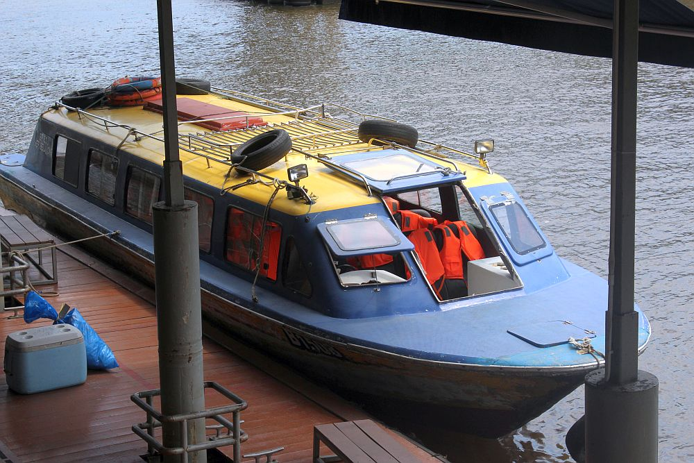 The boat is low to the water, painted blue, with a yellow roof with a luggage rack on it. Inside a few of the seats are visible, with bright orange life vests draped on them.