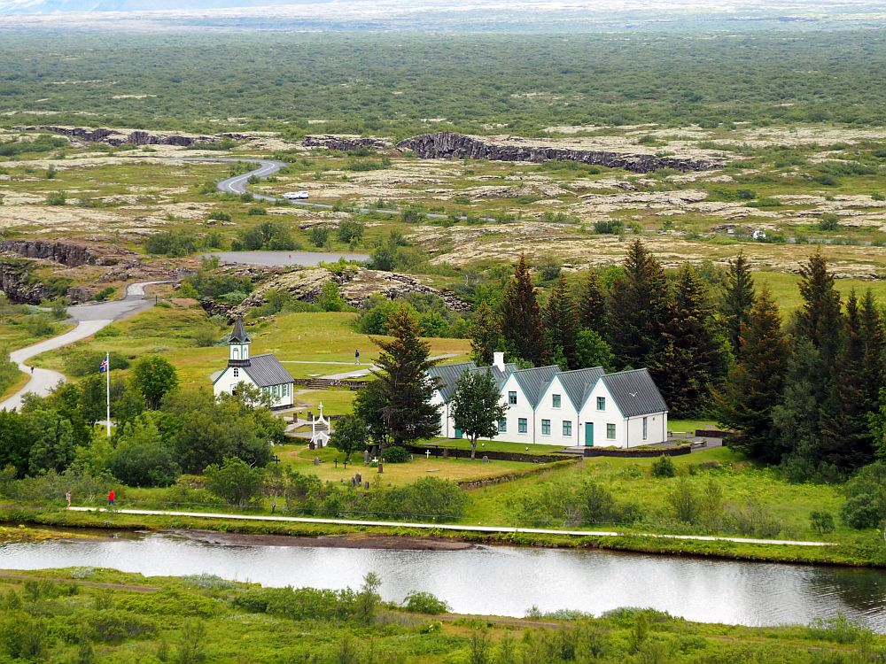 View into the valley with the church and prime minister's house in the center. In front of them, a small river. Behind them flat land stretches for a long way, some of it rocky, the rest green. About halfway to the top of the picture from the building is a crack in the ground with some rock walls showing.