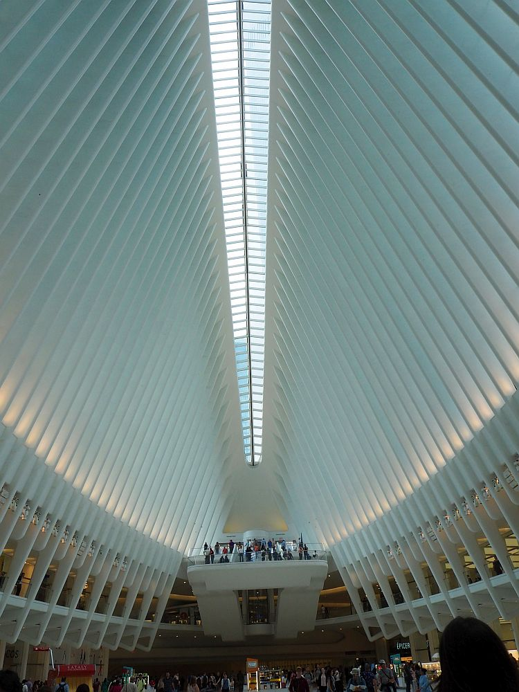 A soaringly high ceiling extends ahead, with a large stairway and some very small people visible at the far end. Along the top, the peak of the ceiling, is a double row of windows letting light in. The side walls are ribbed with vertical ribs.