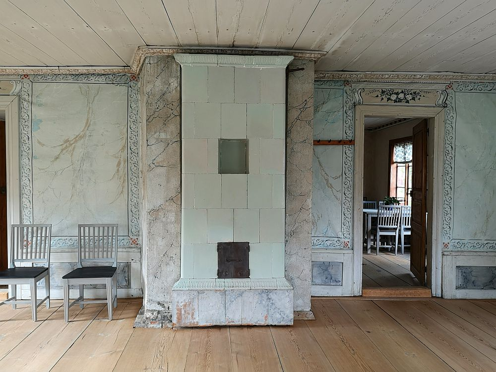 The walls here are light blue, with brown fake marbling across each. The edges have a simple pattern painted on them in a darker blue. A flowery garland in white and blue above the doorway. IN the center is a tiled furnace in a very simple floor-to-ceiling style.