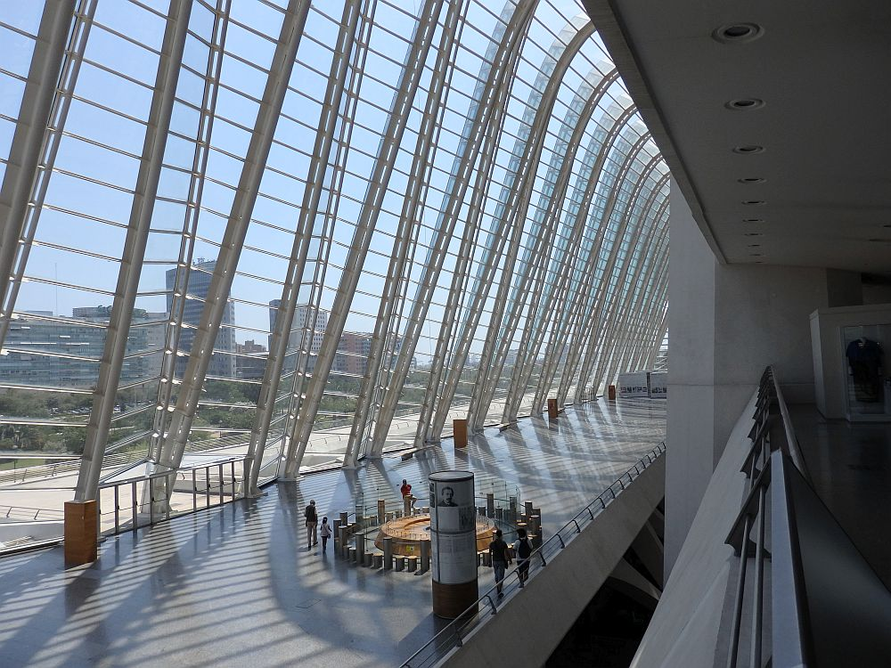 Looking from a balcony down into a very long hall with a wall of ribs of glass that extend up out of sight above. Below is a group of people, looking very small in that vast space.