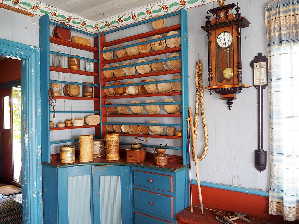 In the corner is a cupboard with cabinets and drawers below and plate rails all the way to the molding above. The whole thing is painted in bright blue, light blue and deep red. Next to it a large clock hangs on the wall. A flowery molding lines the ceiling above.