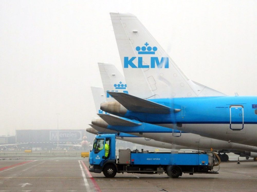 A row of KLM planes parked on the runway: Just their tails, in a neat row, are visible here, with one service truck parked under the nearest one.