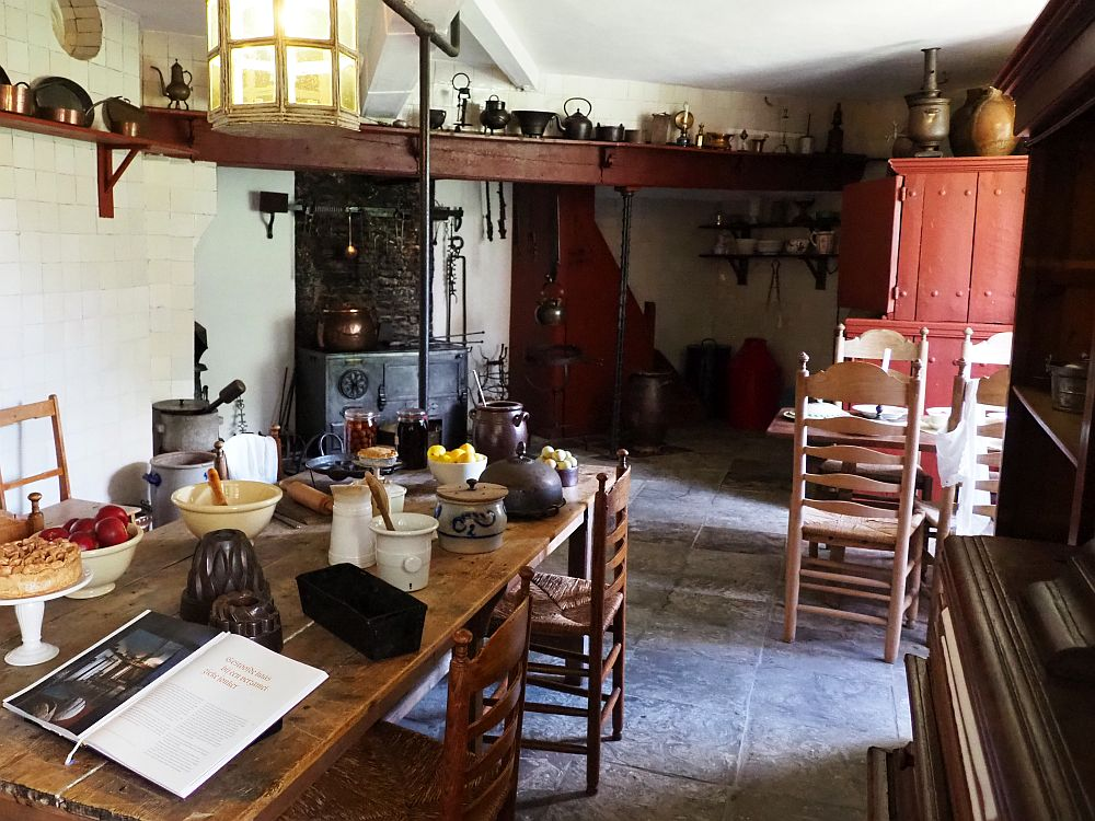 Foreground, a long wooden table with various food preparation tools on it like morters and pestles. Beyond, a cast-iron stove in the far corner. On the wood beam above it are various other tools: kettles and pots and such. On the right halfway down the room part of another wooden table with chairs around it is visible, and a large cupboard beyond that. The floor is rough stone and the walls are plain white.