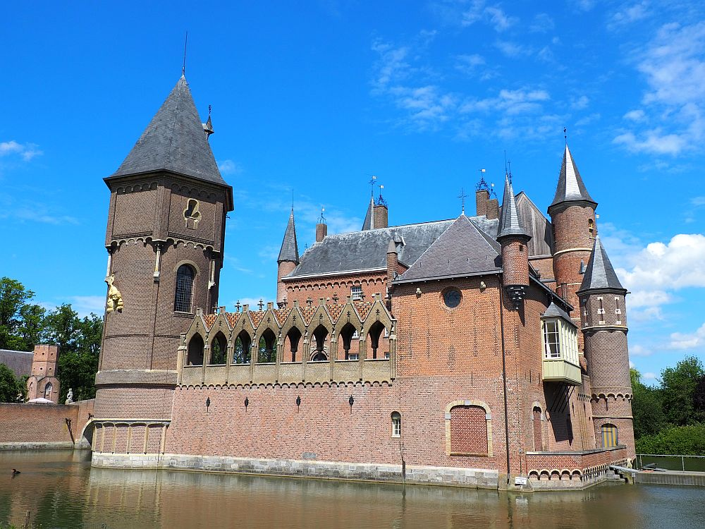 In this view of the castl, it is entirely surrounded by a moat. The biggest tower is on the left and is connected to the smaller tower on the right by a walkway with decorative roofing with arched openings. On the far side are several more, smaller turrets.