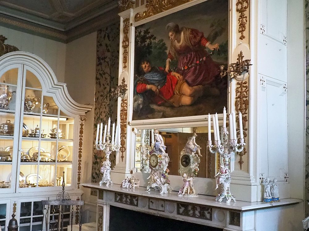 On the right is a grand mantel with two clocks in the center made of white porcelein, very flowery. One other end is a white porcelein candelabra with multiple candles. Behind the clocks is a mirror and above that a painting with two figures, one liying down, another leaning over the first on her knees. Around the painting is gold-painted edging. Left of the mantal is a large glass-fronted cupboard with a rounded top, lit from inside, where various china and silver is on display.