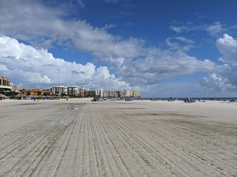 A view along the wide white-sand beach. In the foreground, the sand is flat and empty and looks like it's been raked. In the background, a cluster of tall buildings, presumably hotels and apartments. A bit of the ocean is visible on the right. White fluffy clouds and blue sky.