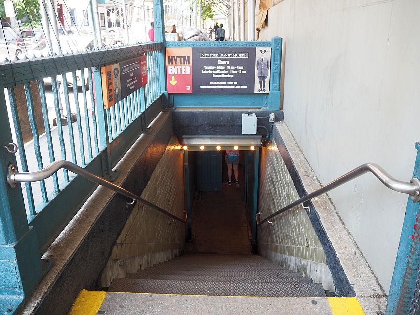 """Looking down a stairway with a wall on one side and a rail on the other. A small sight on the rail straight ahead says """"New York Transit Museum"""" and lists the museum's opening hours."""