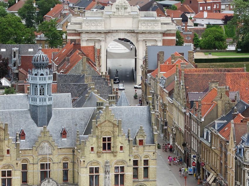 A view of Ypres from a tower. It shows a road with beautiful old buildings lining it, and a large arch over the road: the Menin Gate.
