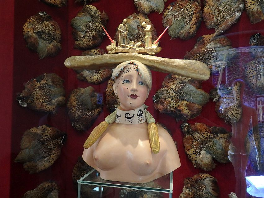 A sculpture of a woman from just under her breasts and up. She is naked, breasts exposed. Around her neck is a band with a human figure on it who appears to be jumping. An ear of corn sits on either shoulder, hanging in front like pigtails. She has ants crawling on her forehead and down to her mouth. On her head is a long horizontal loaf of bread: a baguette. On top of that is a carved scene: two men, both looking down, one holding his hat in front of him. It is not clear what they are looking at.