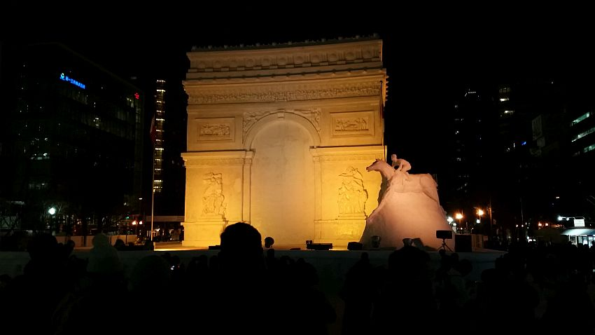 The large snow sculpture shown is lit in a yellowish light against the darkness of light. It is a large building with an arch - perhaps the Arc de Triomphe, with detailed bas-relief detail on it. To its right is a sculpture of a man riding a horse.