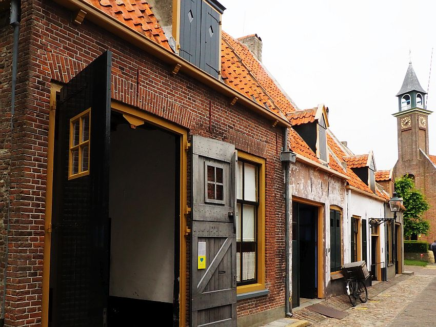 Looking down a row of building. The nearest is red brick with orange trim and large open doors that look like barn doors.The buildings behind them are houses, very small, each with a door and one window on the ground floor and one dormer window upstairs. A church tower is visible beyond them.